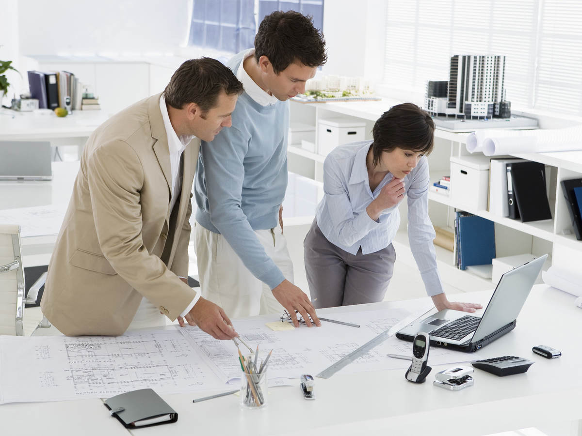 Three people in an office confer over computer and floor plans.