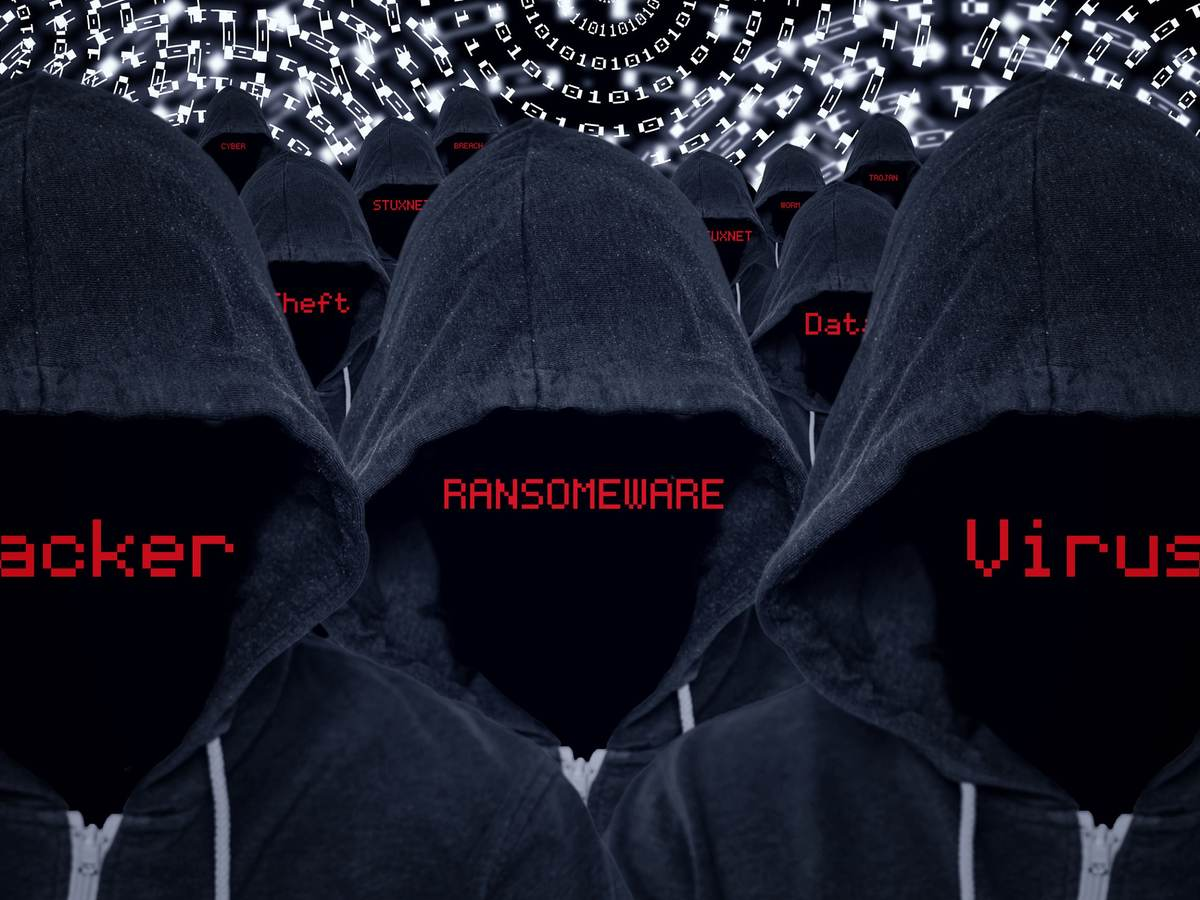 Mass of hooded computer criminals with various internet attacks and criminal activities in red text with a binary code background