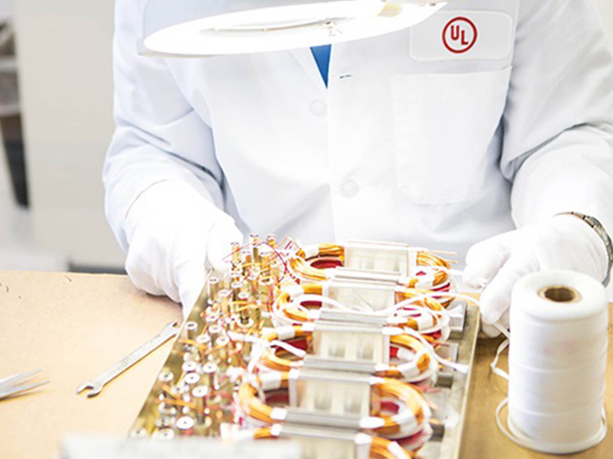A UL laboratory worker examining a wire board.