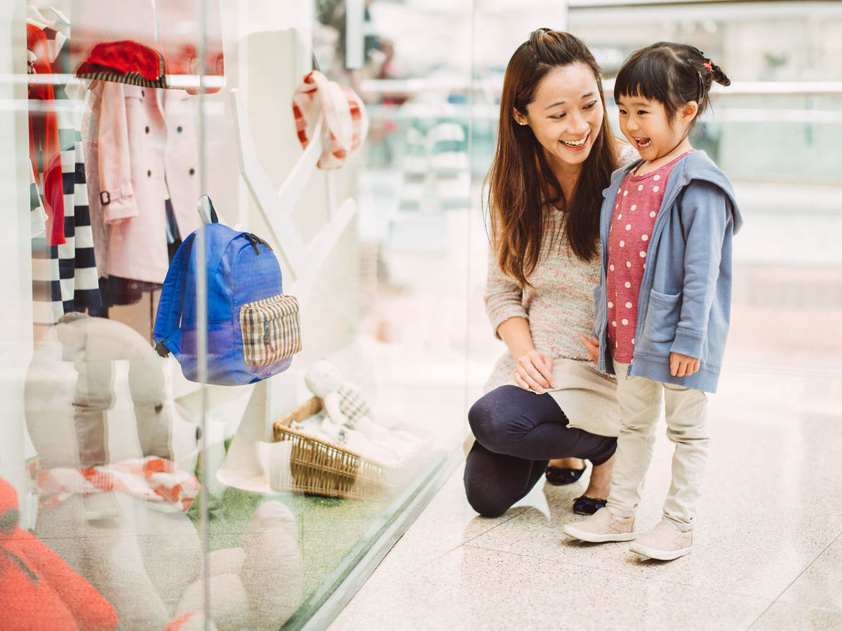 A mother and her daughter look at a clothing store window display in China.