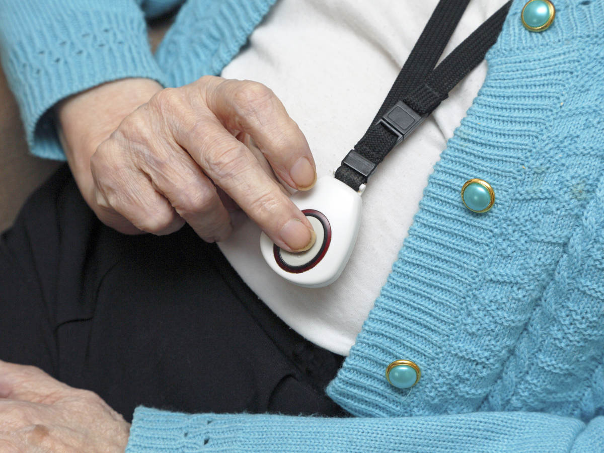 Elderly woman demonstrating call button worn on neck strap