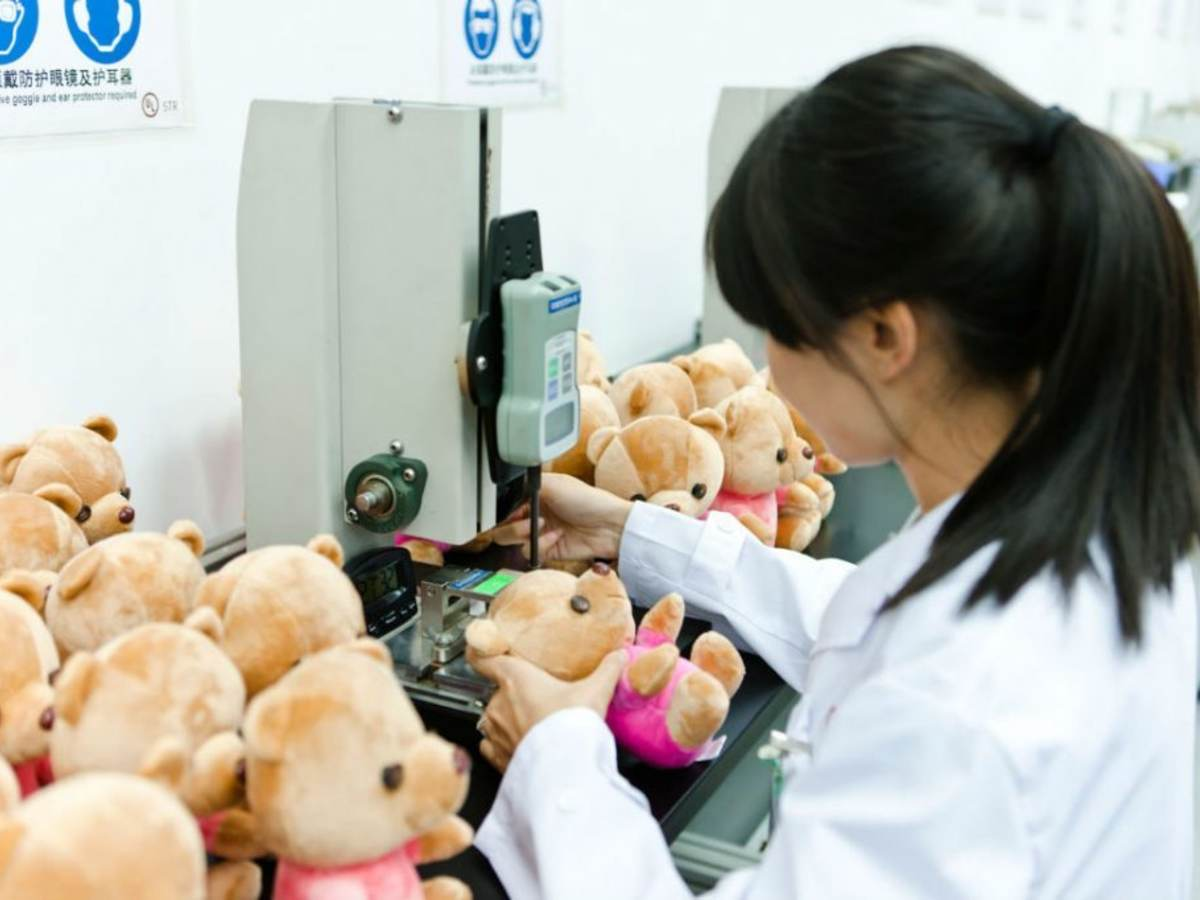 Factory worker making teddy bears.
