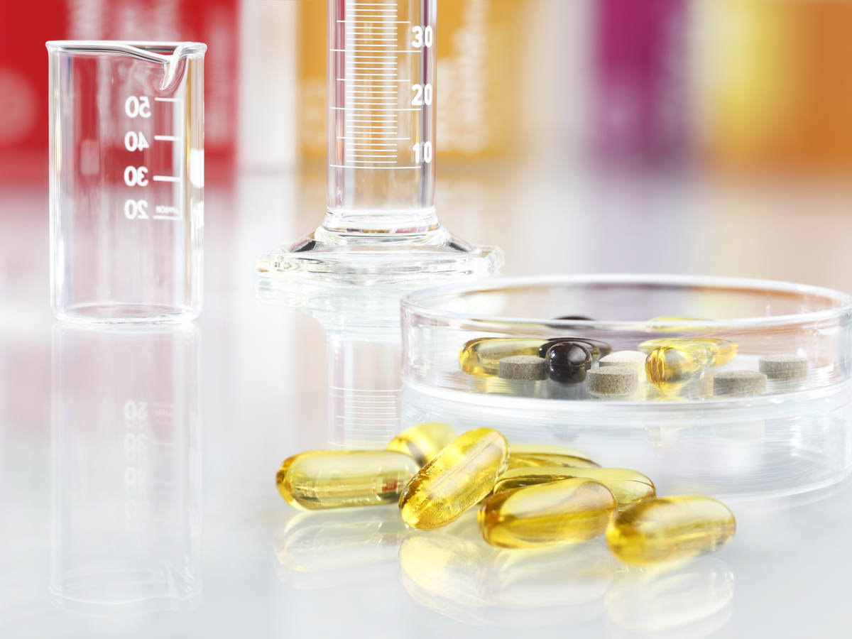 A close-up image of yellow pills on a lab table next to measurement vials.