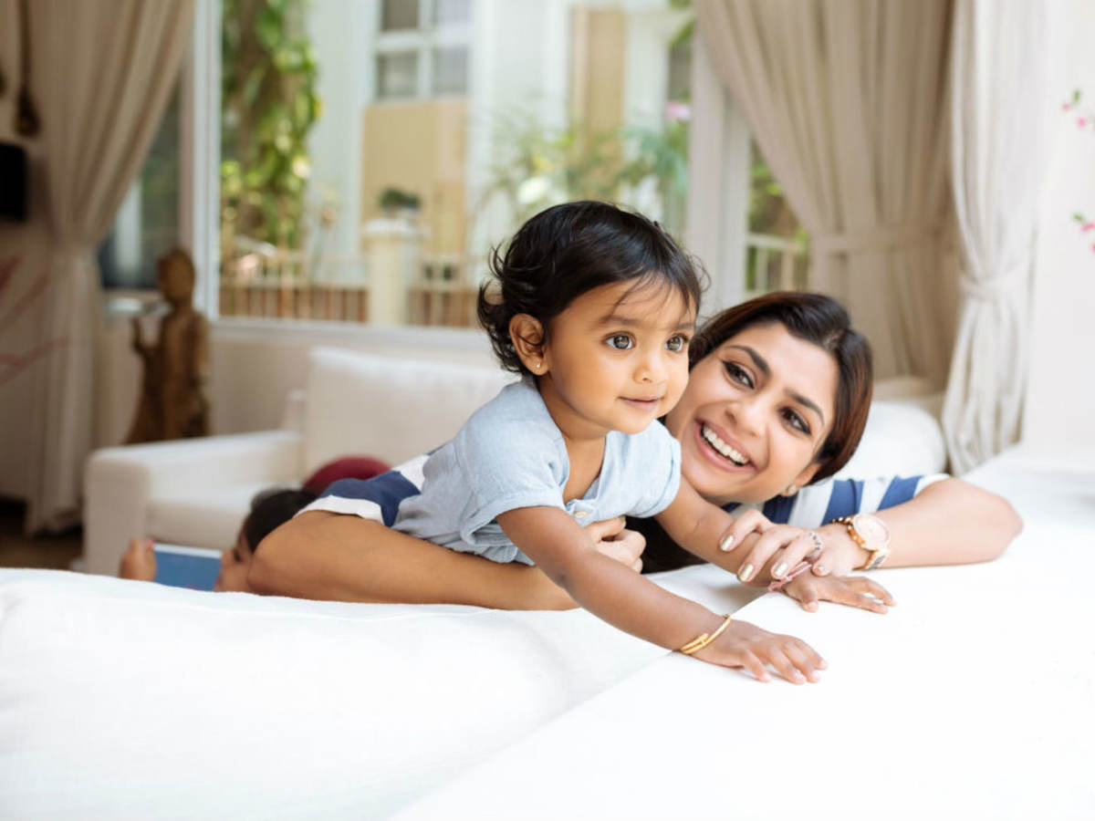 A smiling mother and child sitting on a couch while looking out the window.