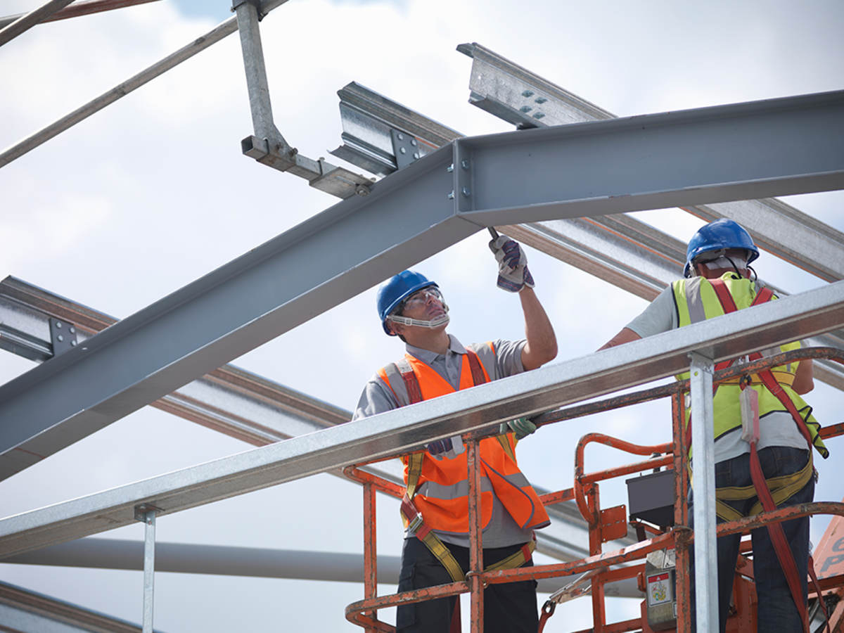 A construction worker laboring on a steel structure