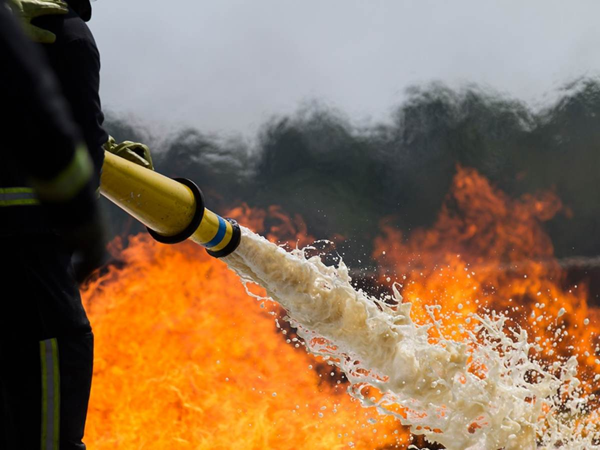 Firefighter spraying a fire with foam hose