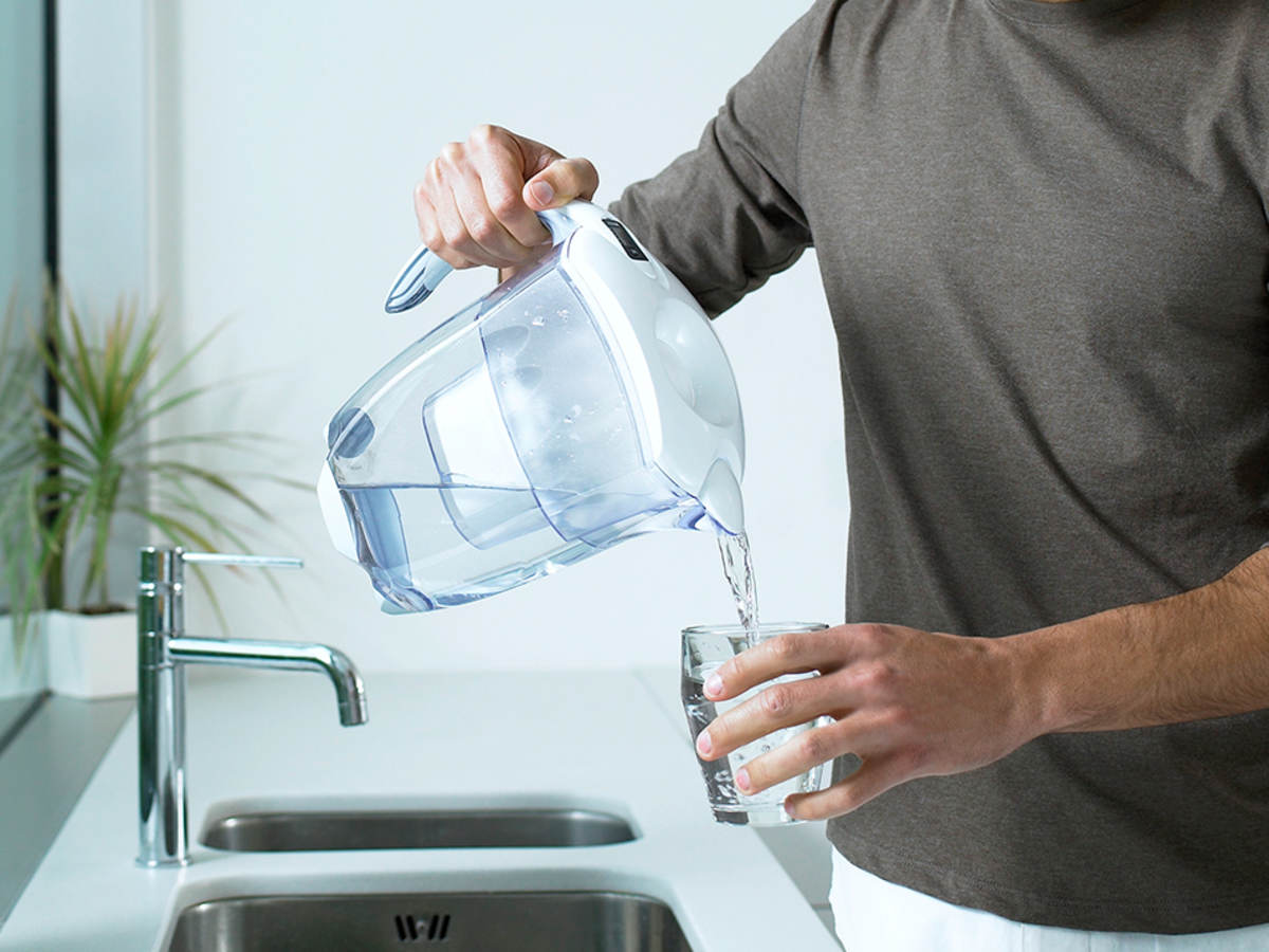 Man pouring water from a water filter pitcher