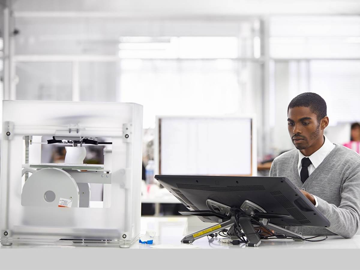 Man designing a product being printed on a 3D printer