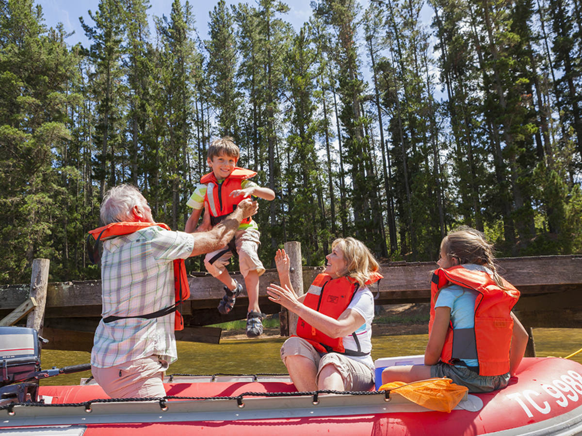 A family wearing orange life jackets boarding a boat.