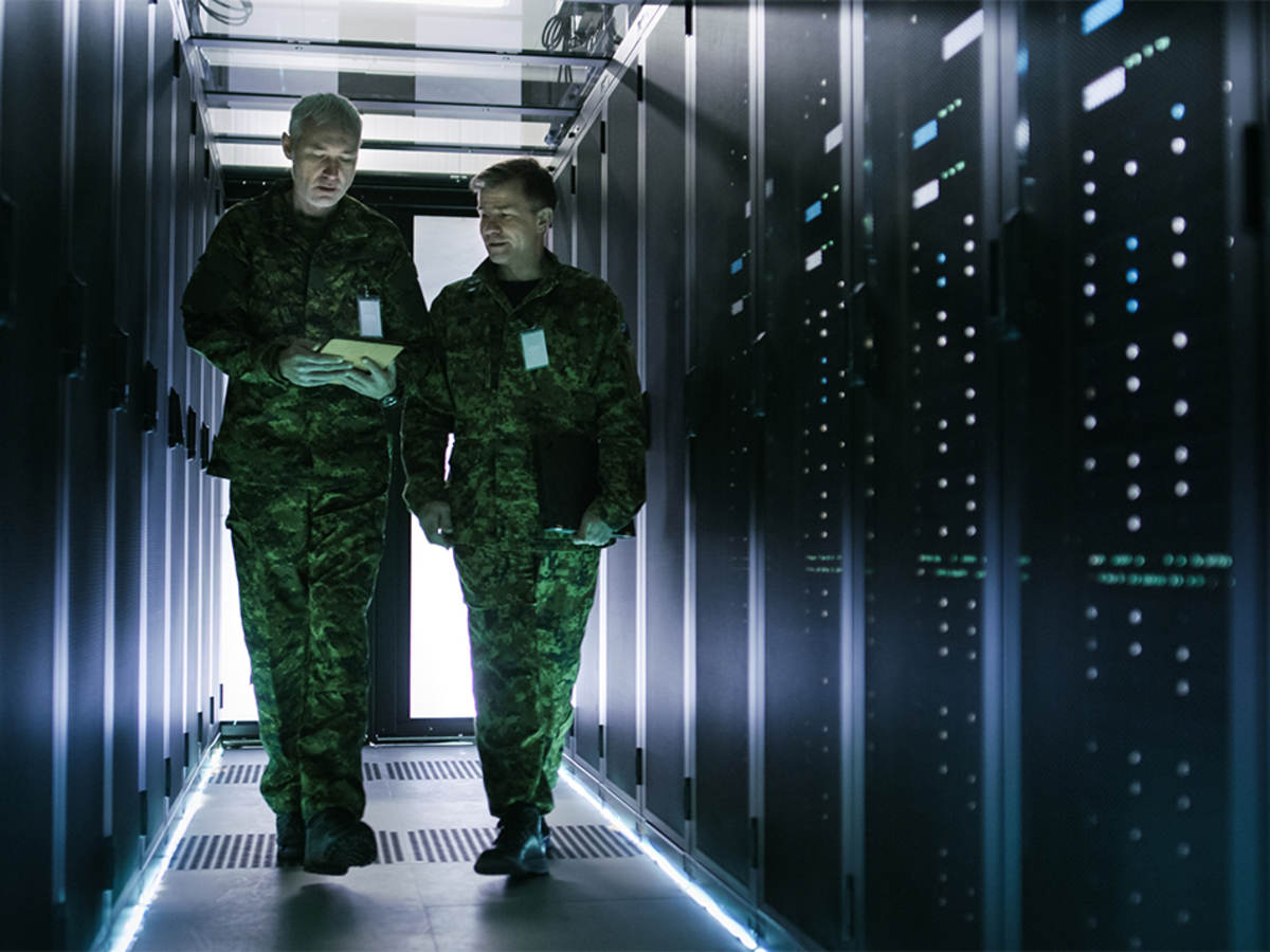 Two military men walking in data center corridor