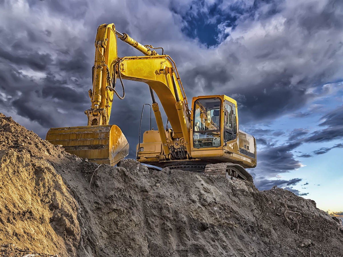 Yellow excavator on dirt hill