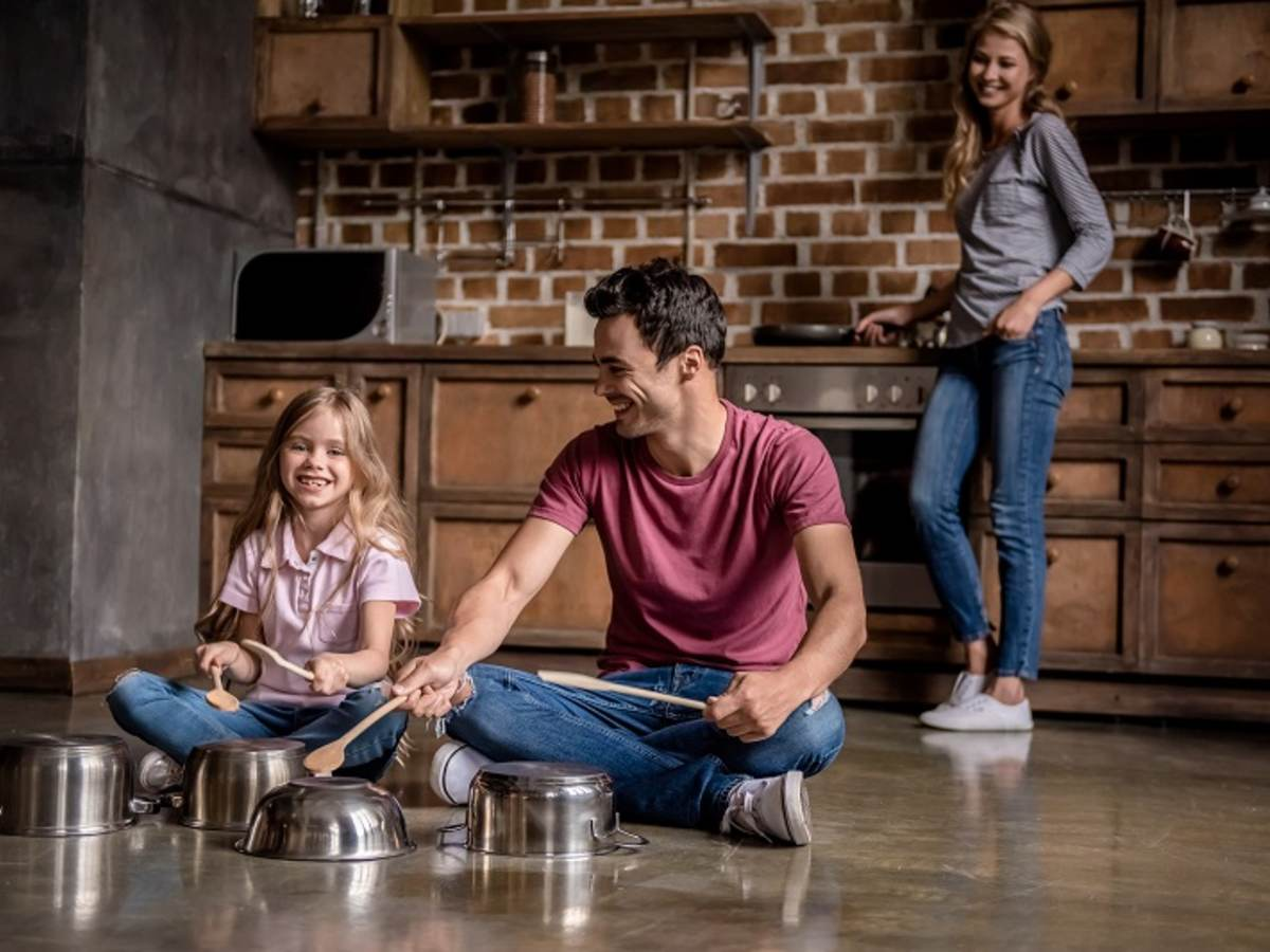 Father and daughter playing percussion on kitchen pots while mother watches from the stove