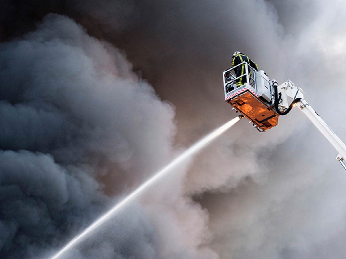 Firefighter on aerial ladder spraying hose against smoky sky