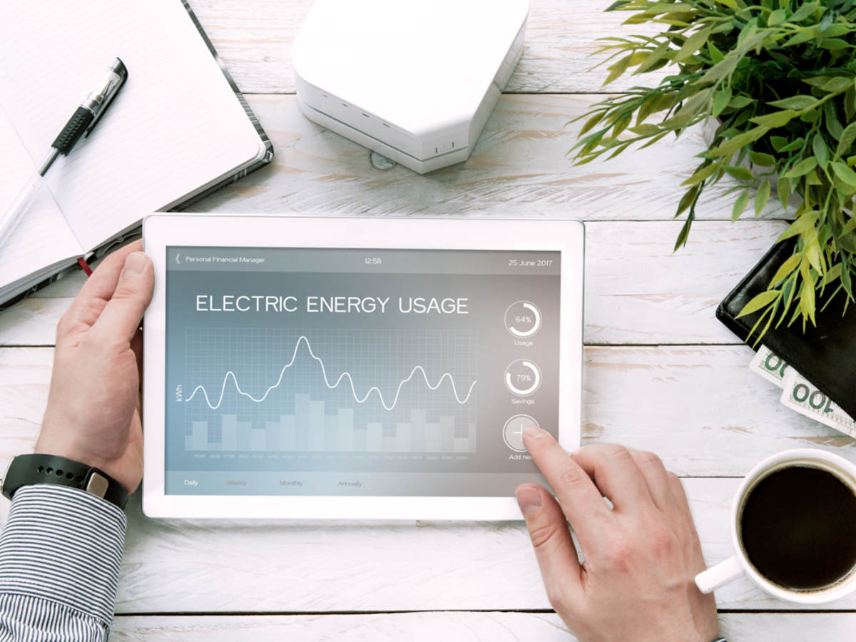 Man holds tablet PC with electric energy usage application