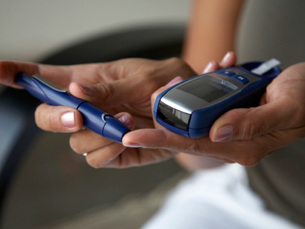 Woman taking blood sugar level w/glucometer