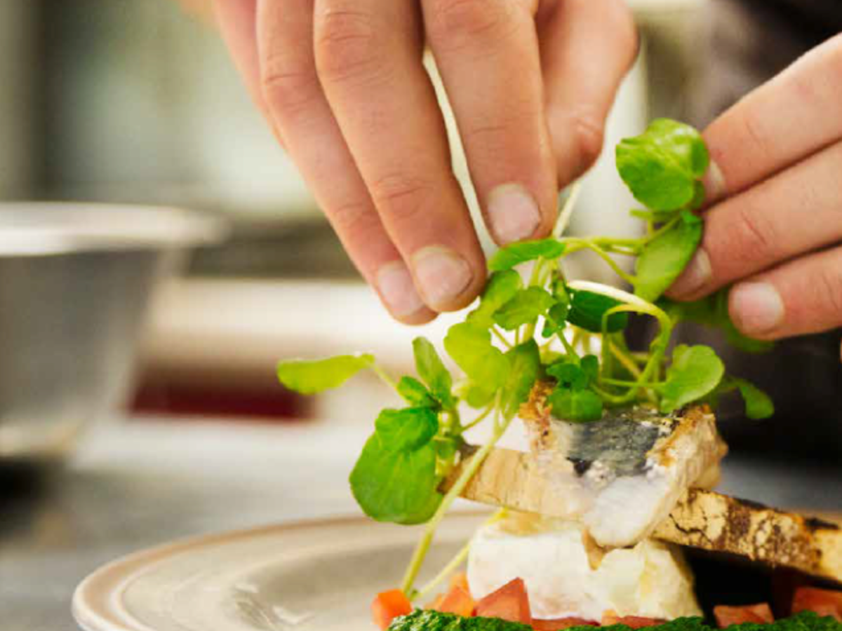 Close up of hands fixing greens on a plate of food