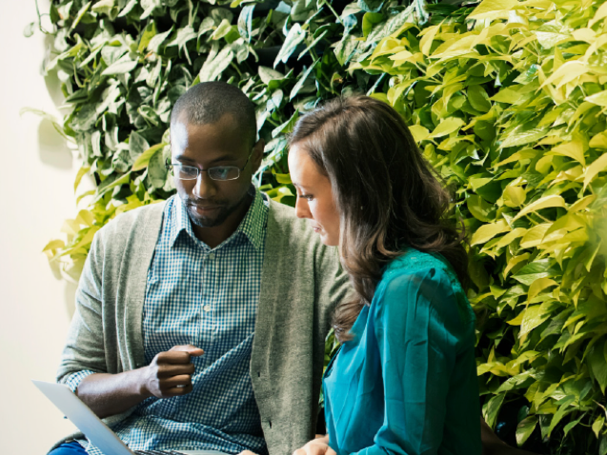 man and woman sitting next to one another in front of foliage