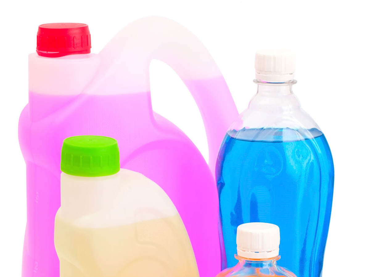 Bottles with different colored cleaning products in them.