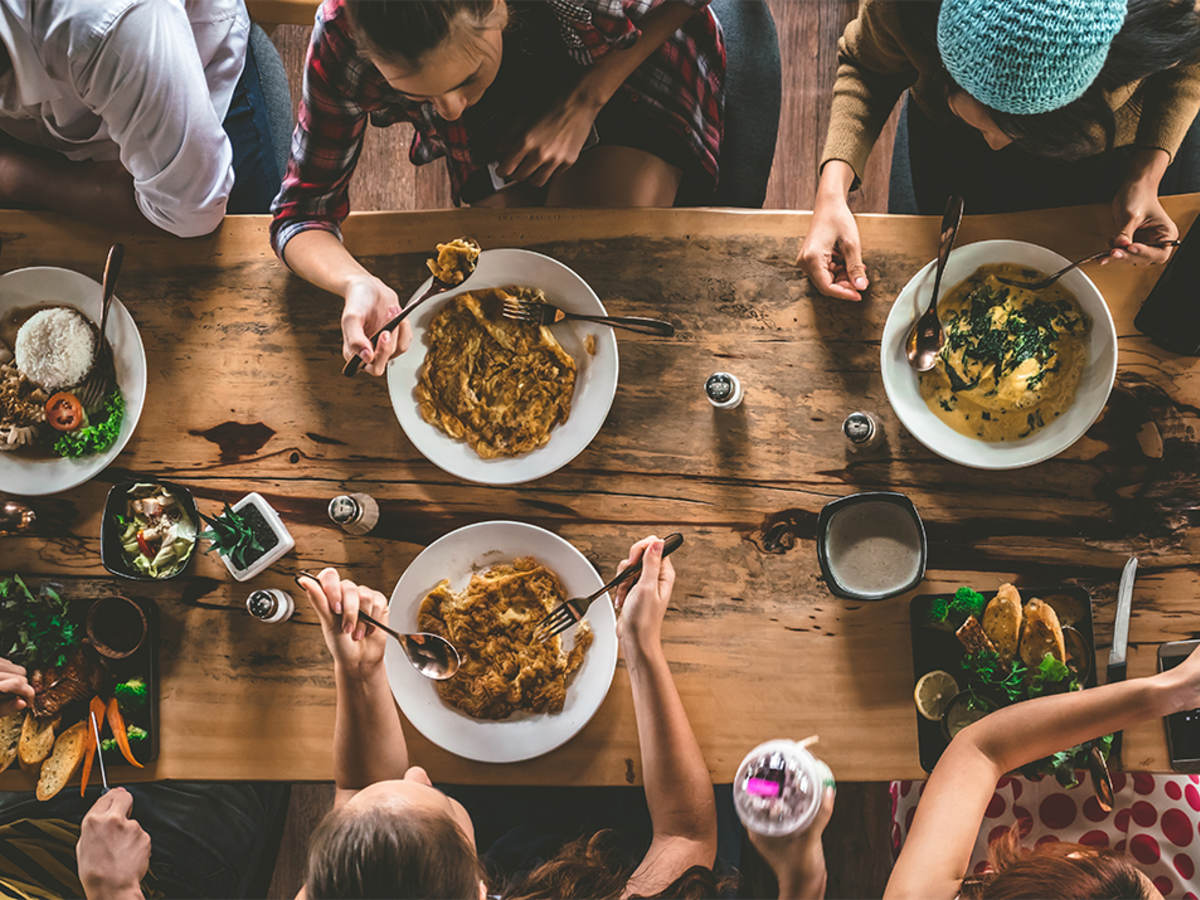 Bird's-eye view of young people eating around a dinner table