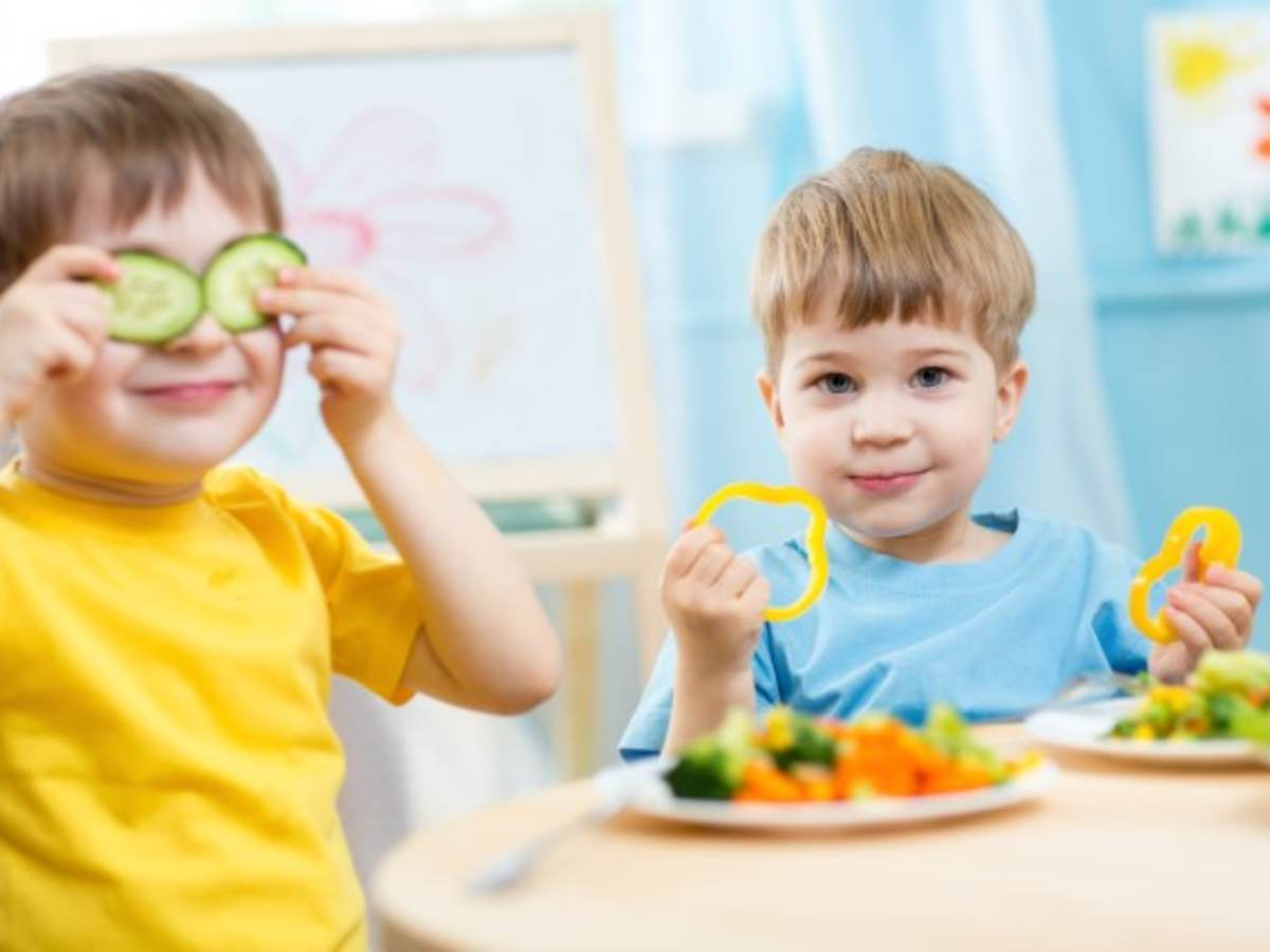 Young boys playing with their plates of vegetables