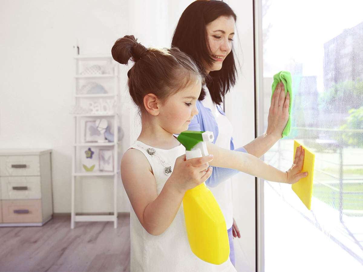 Girl helping her mother clean windows