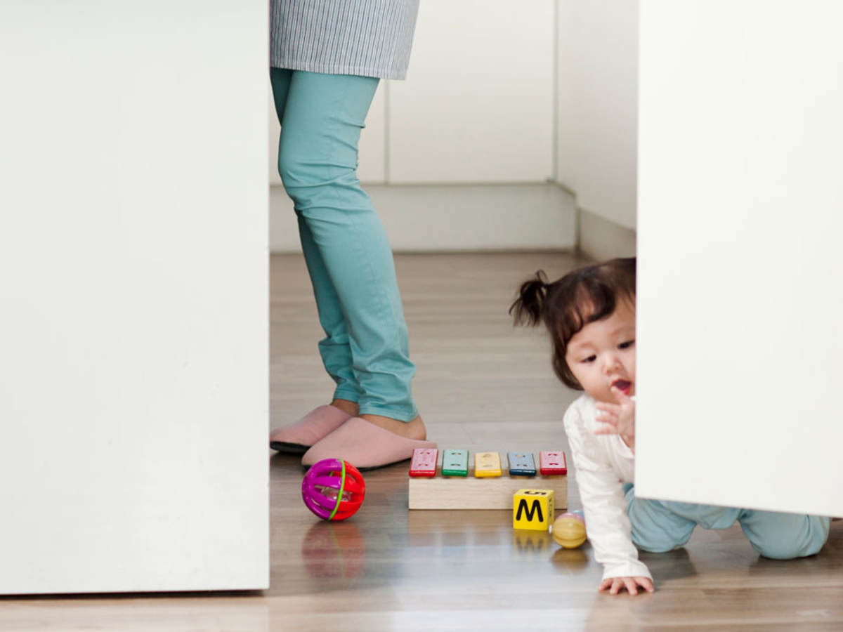 Child playing with toys on the kitchen floor.