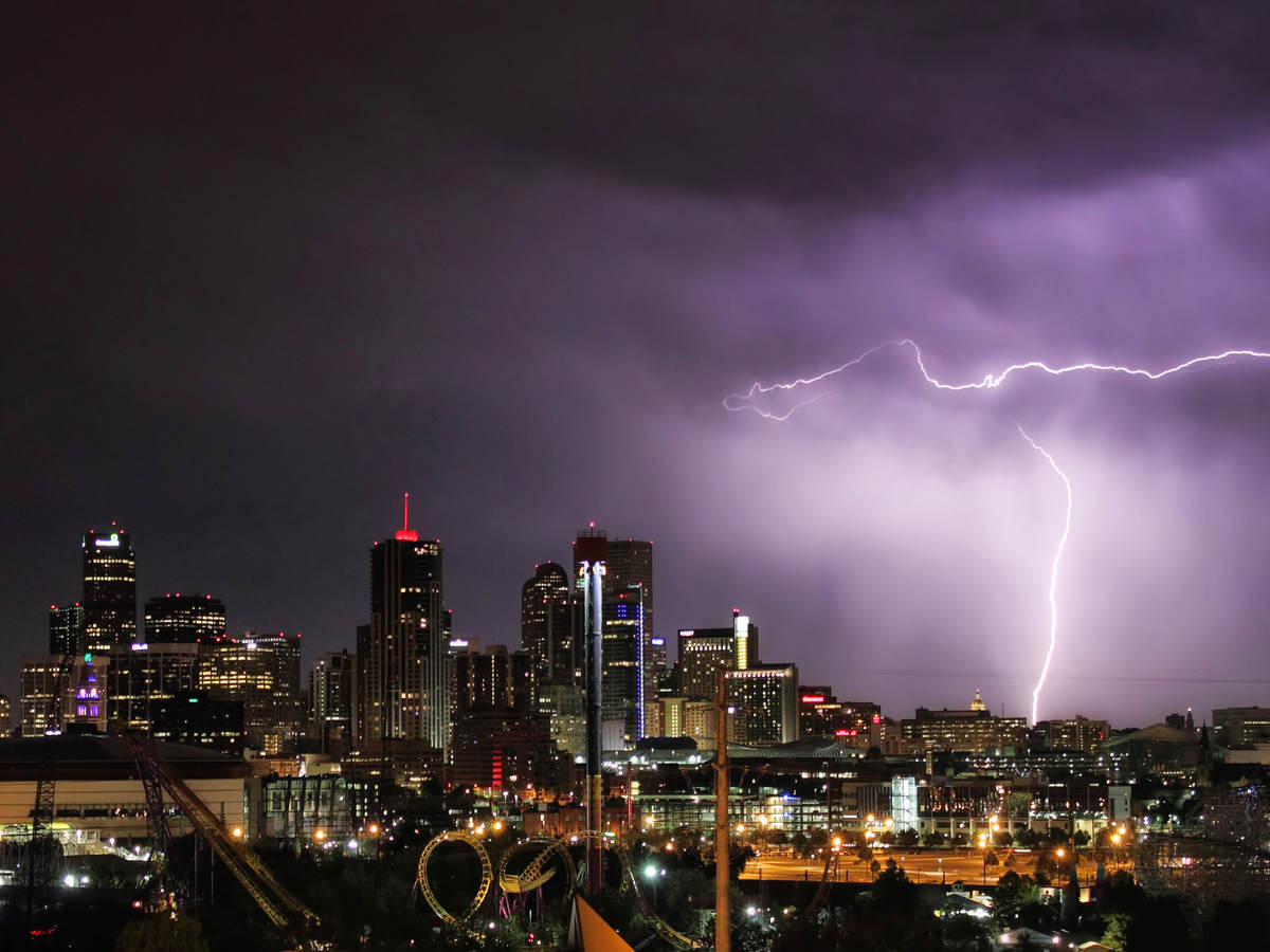 Nighttime skyline with lightning striking a building