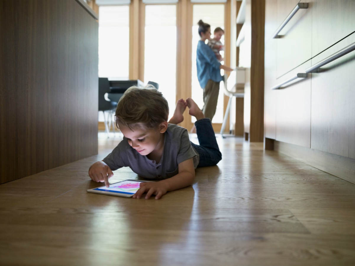 A boy playing with a tablet on the floor in his home.
