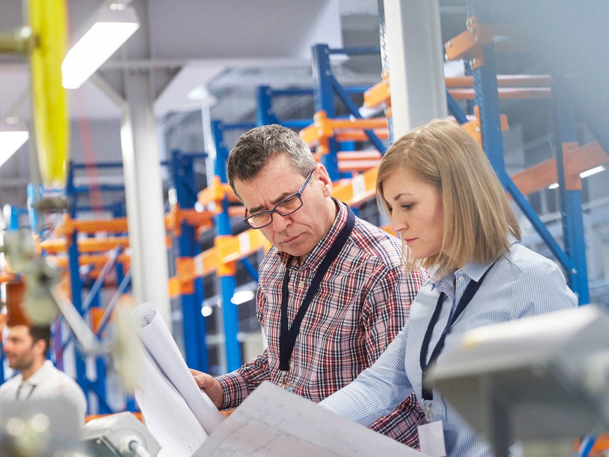 Two people at work looking at printed plans