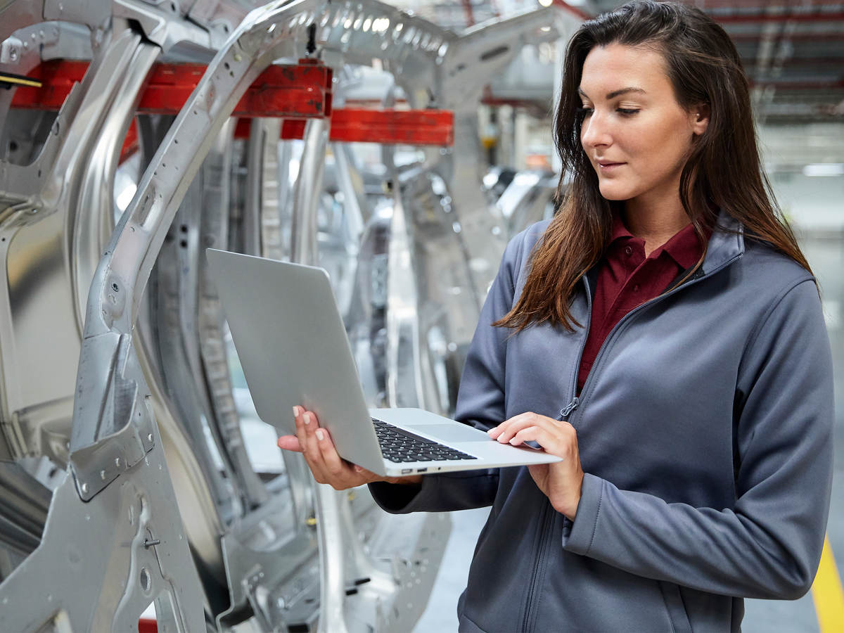 Woman with a laptop inspecting an automotive factory.