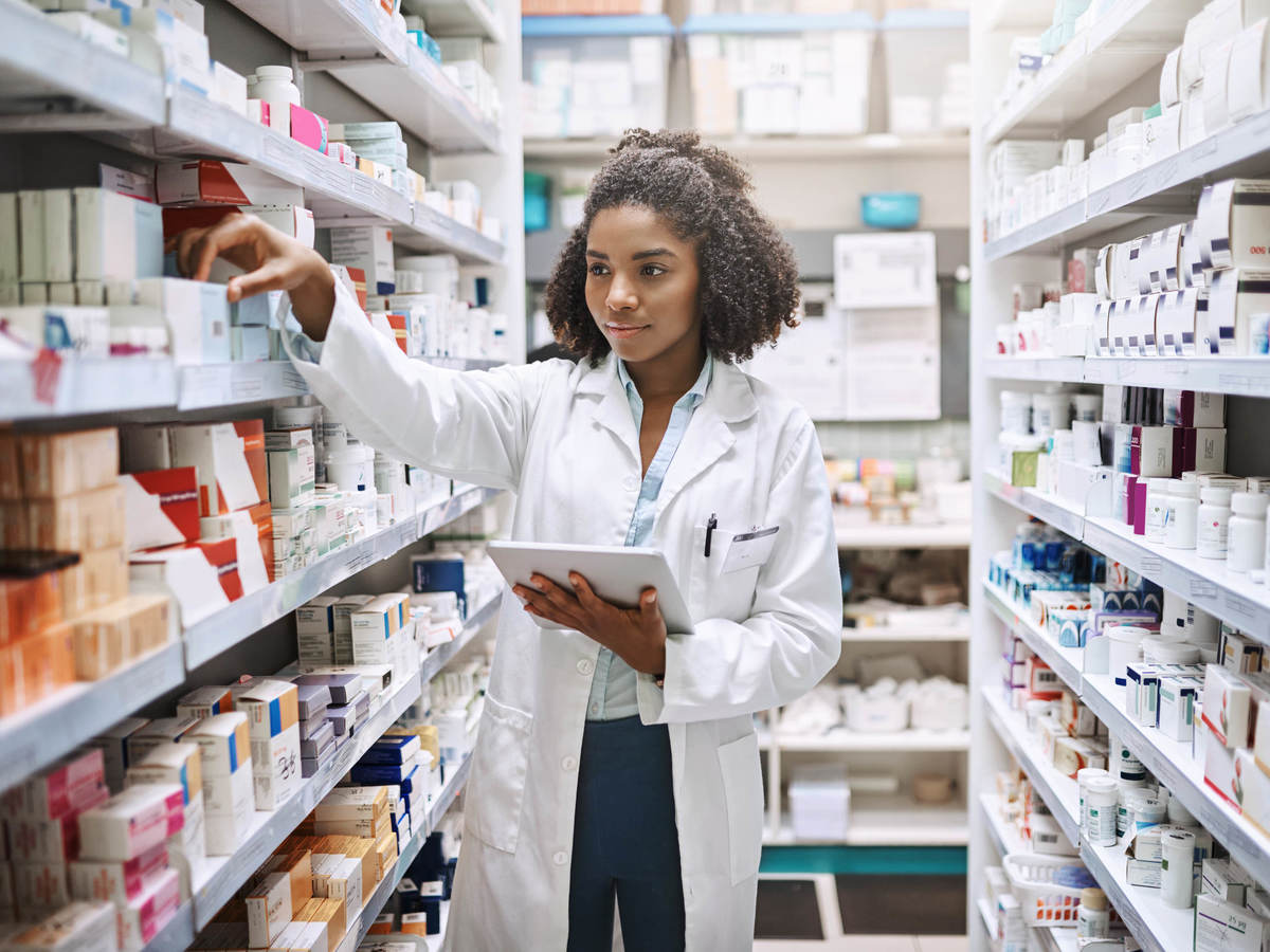 Pharmacist in lab coat looking at items on shelf with tablet in hand
