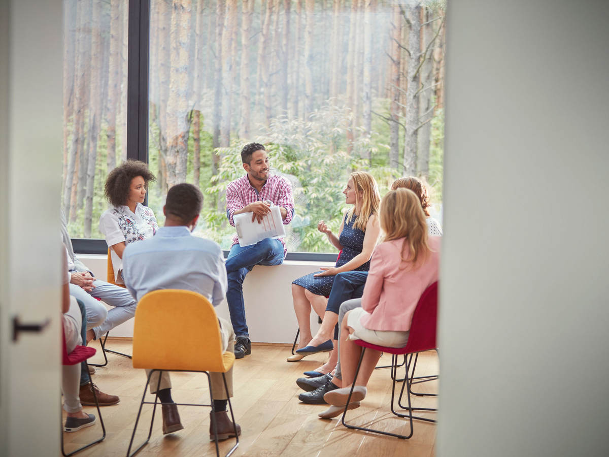 Group of people in an office space sitting in a circle for a meeting