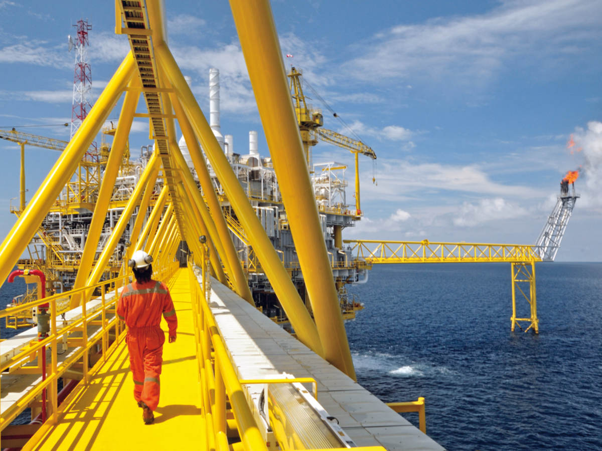 A worker walking on a platform of an offshore rig.