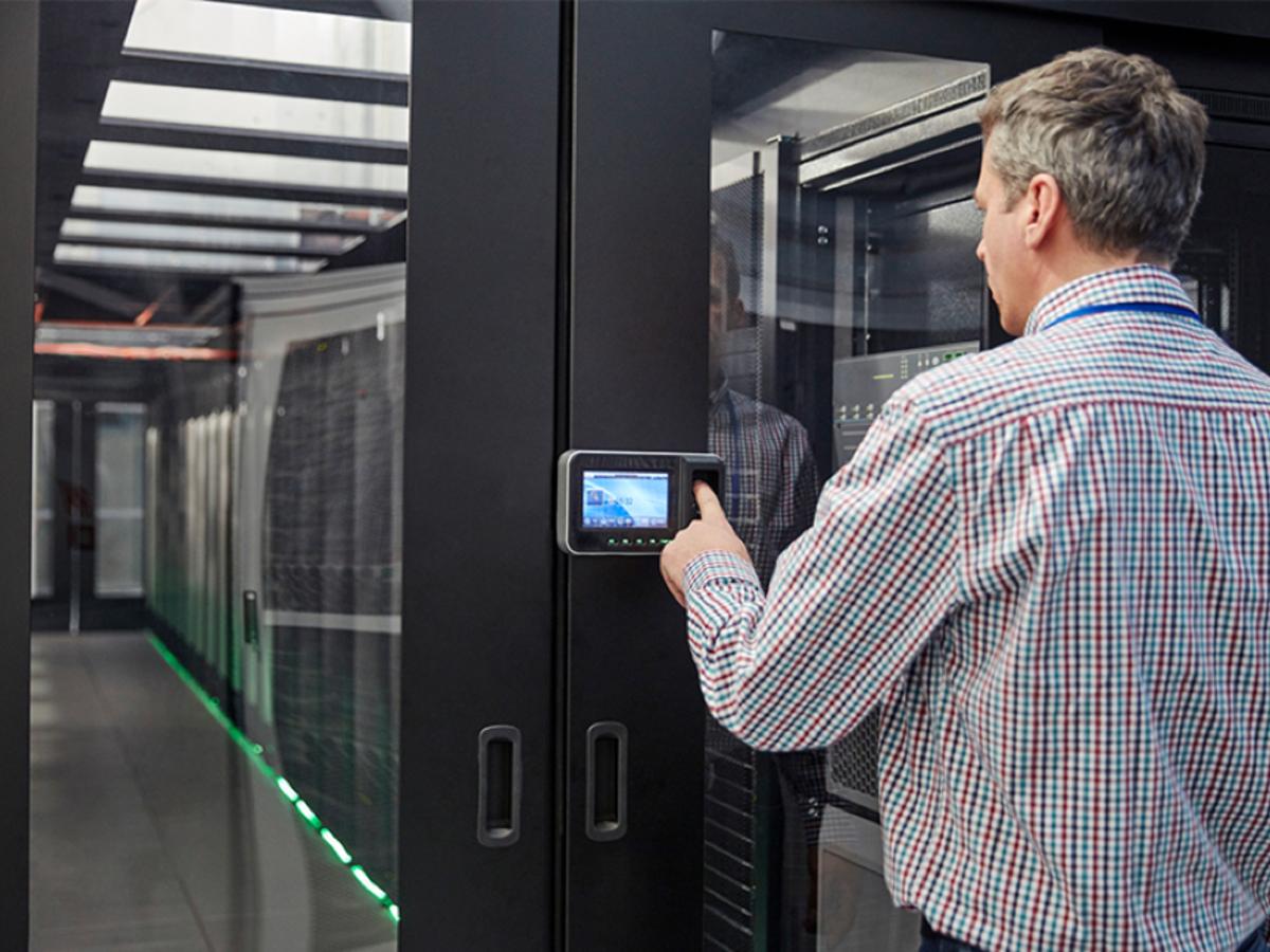 Man entering code on keypad at a room full of servers
