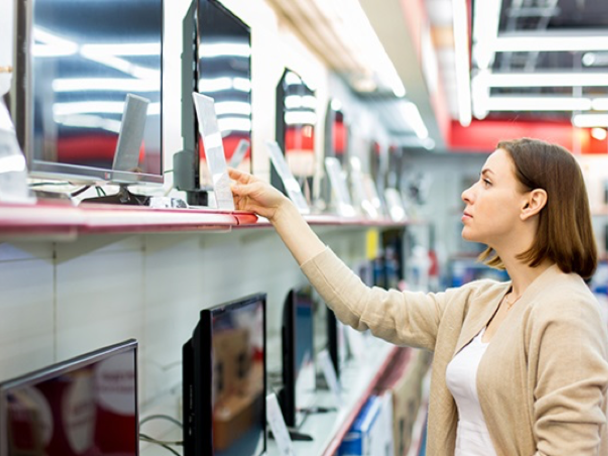 Woman in store looking at monitors on shelf