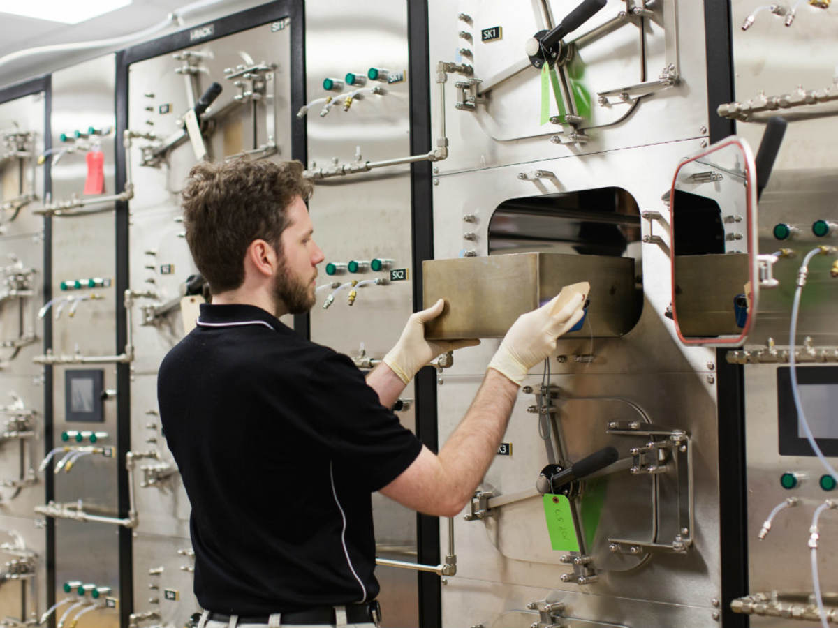 Man using a bank of small testing chambers to determine VOC emissions from products.