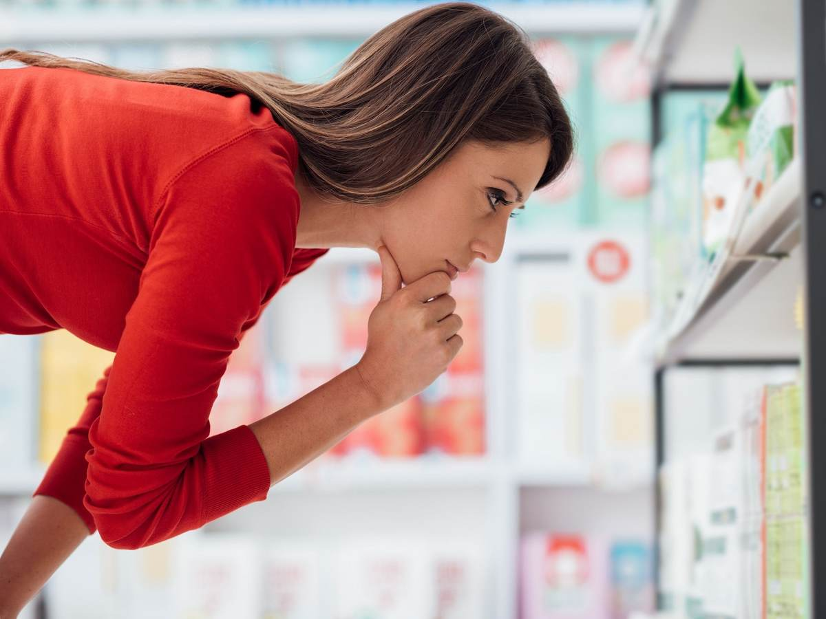 Brown-haired woman looks carefully at a shelf filled over-the-counter medications.
