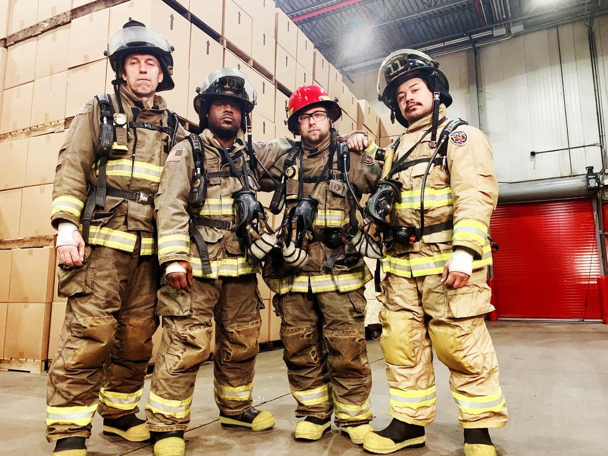 UL firefighters show off their gear in front of a mock warehouse.