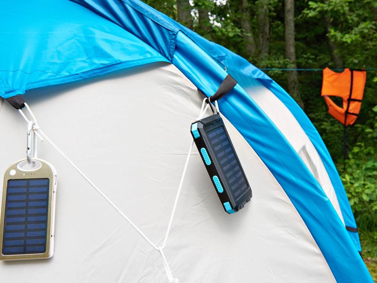 Grey tent with blue roof holds some type of solar panel used to recharge devices.