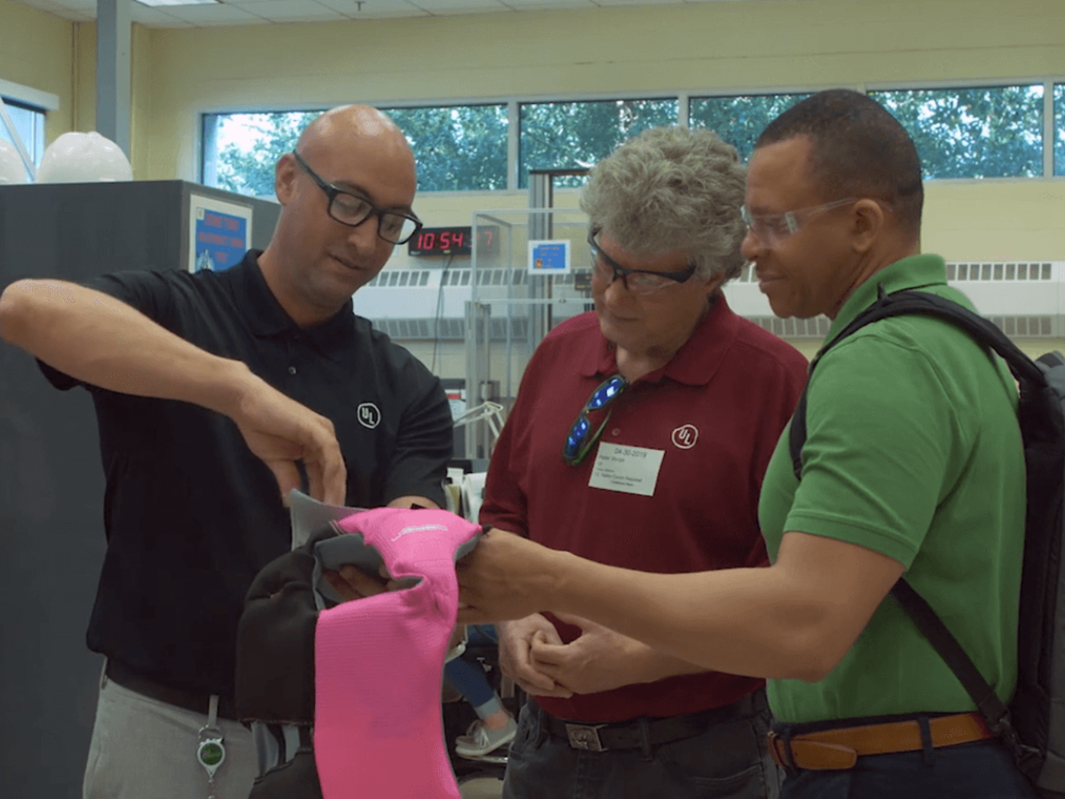 UL staff examines the updated label on a pink life jacket at our Research Triangle Park facility