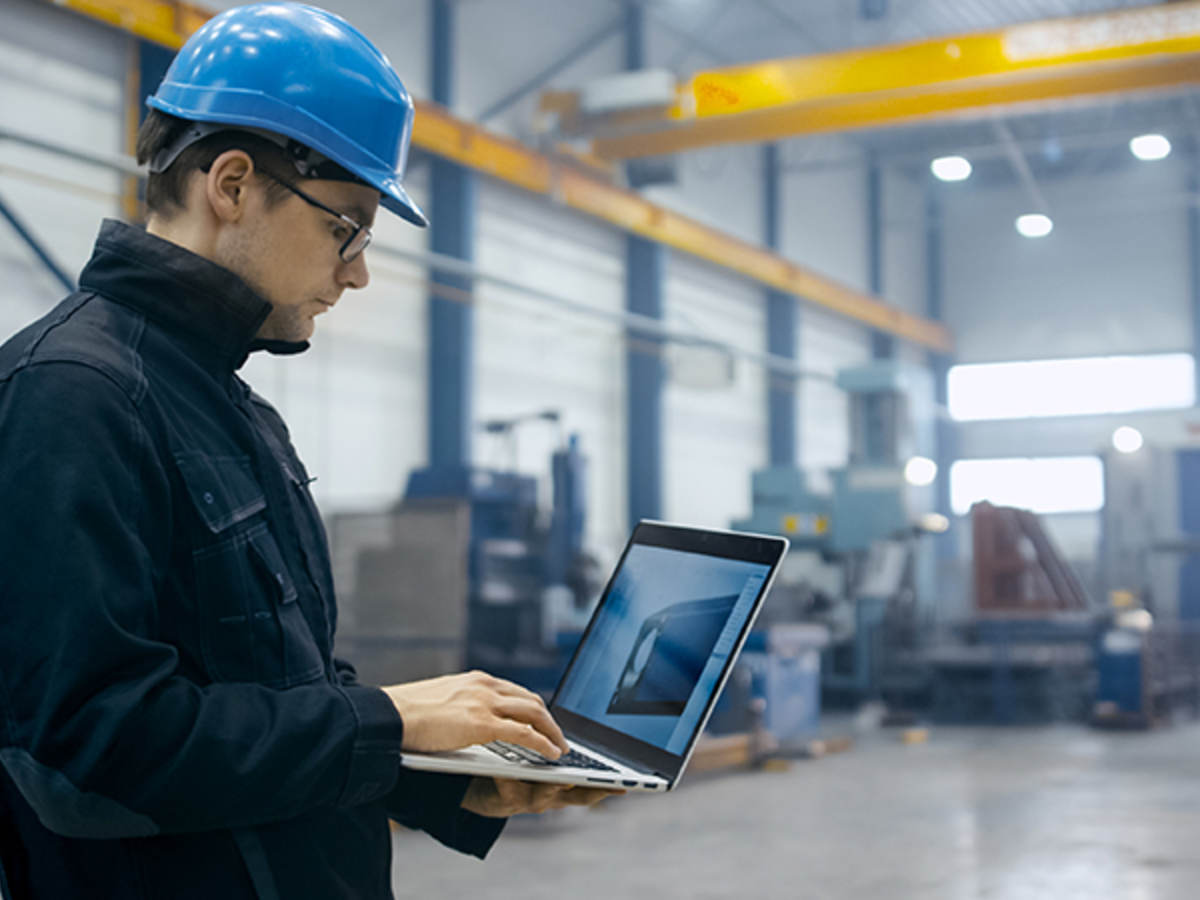 Worker in a hardhat using a laptop