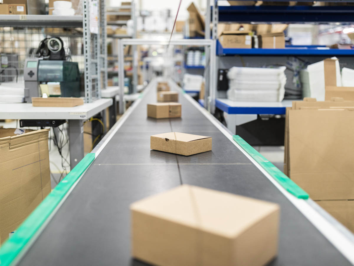 Cardboard boxes on conveyor belt at distribution warehouse
