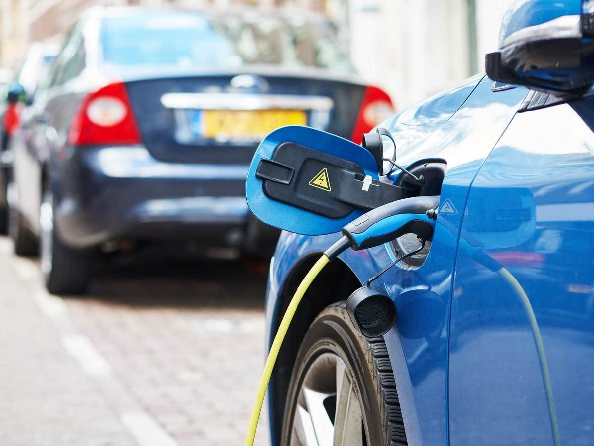 Blue electric vehicle is charging on a city street.