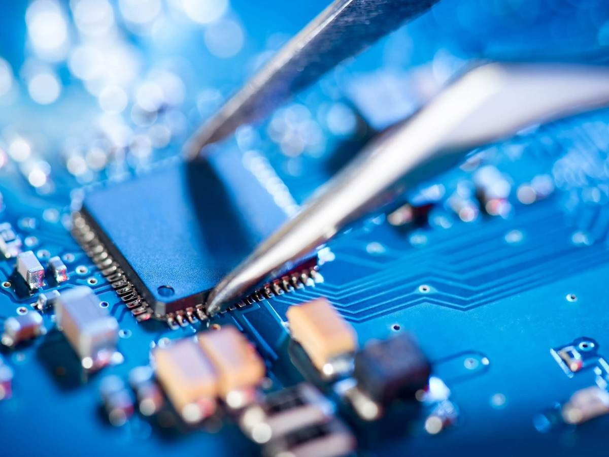 A pair of specialized tweezers places a circuit on a board