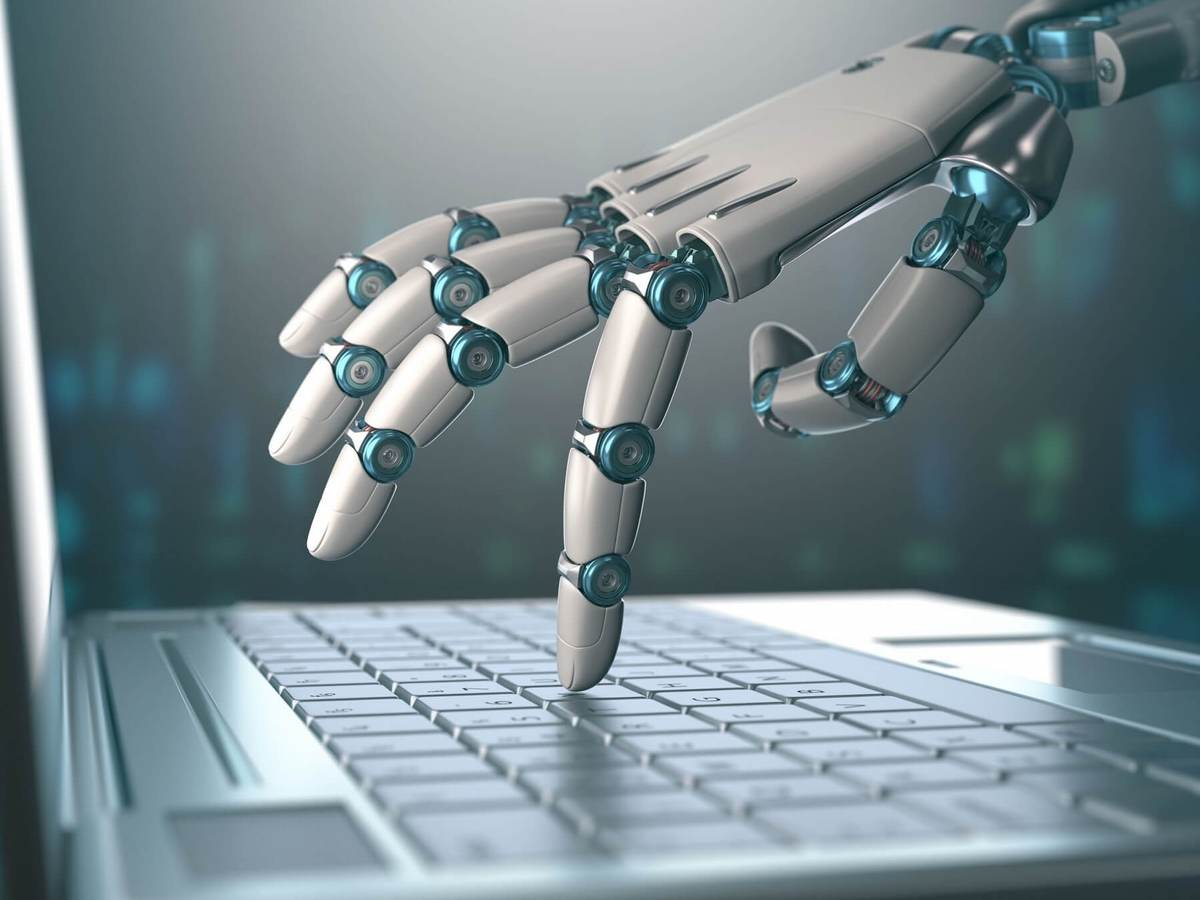 A robotic hand taps keys on a laptop