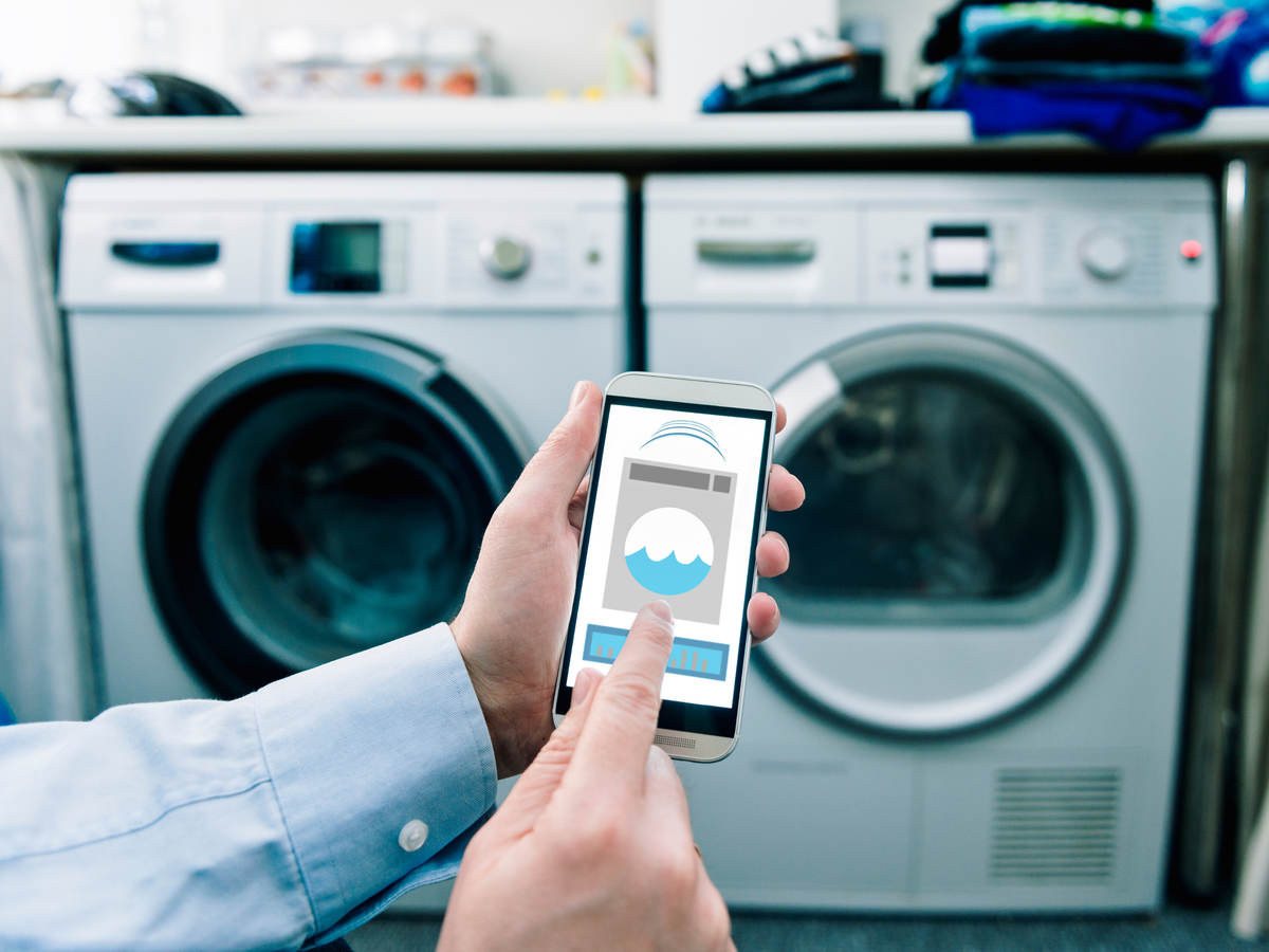 A man using his phone thats connected to a washing machine