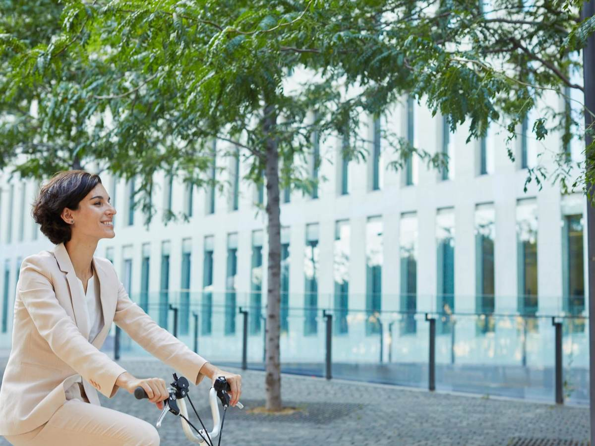 A happy business woman rides a bicycle through a city landscape