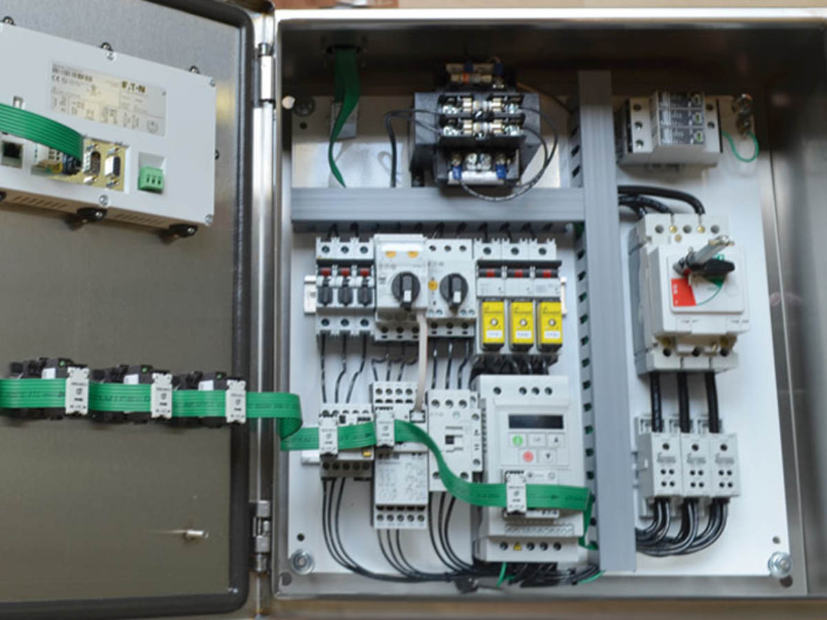 An opened industrial control panel showing components