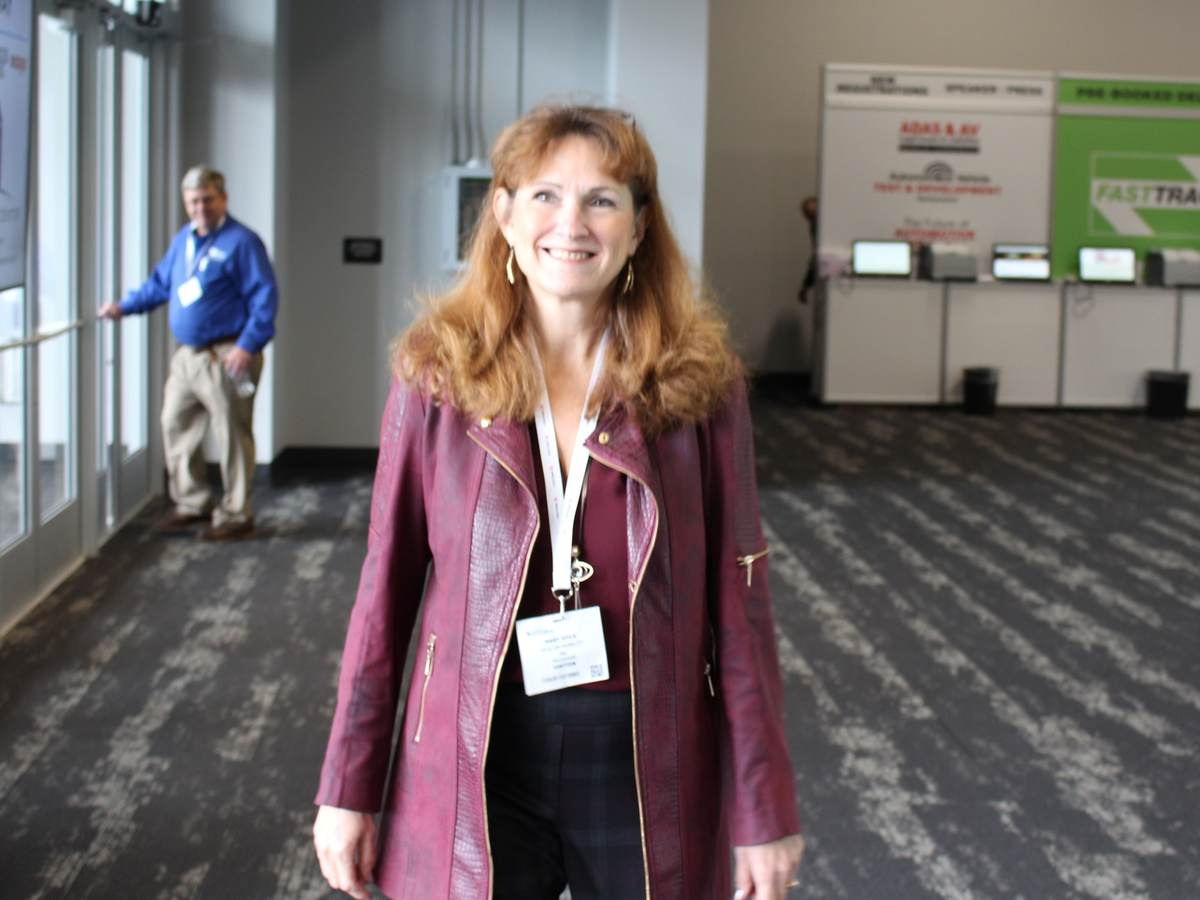 Woman wearing a burgundy jacket with black pants walks around event showroom