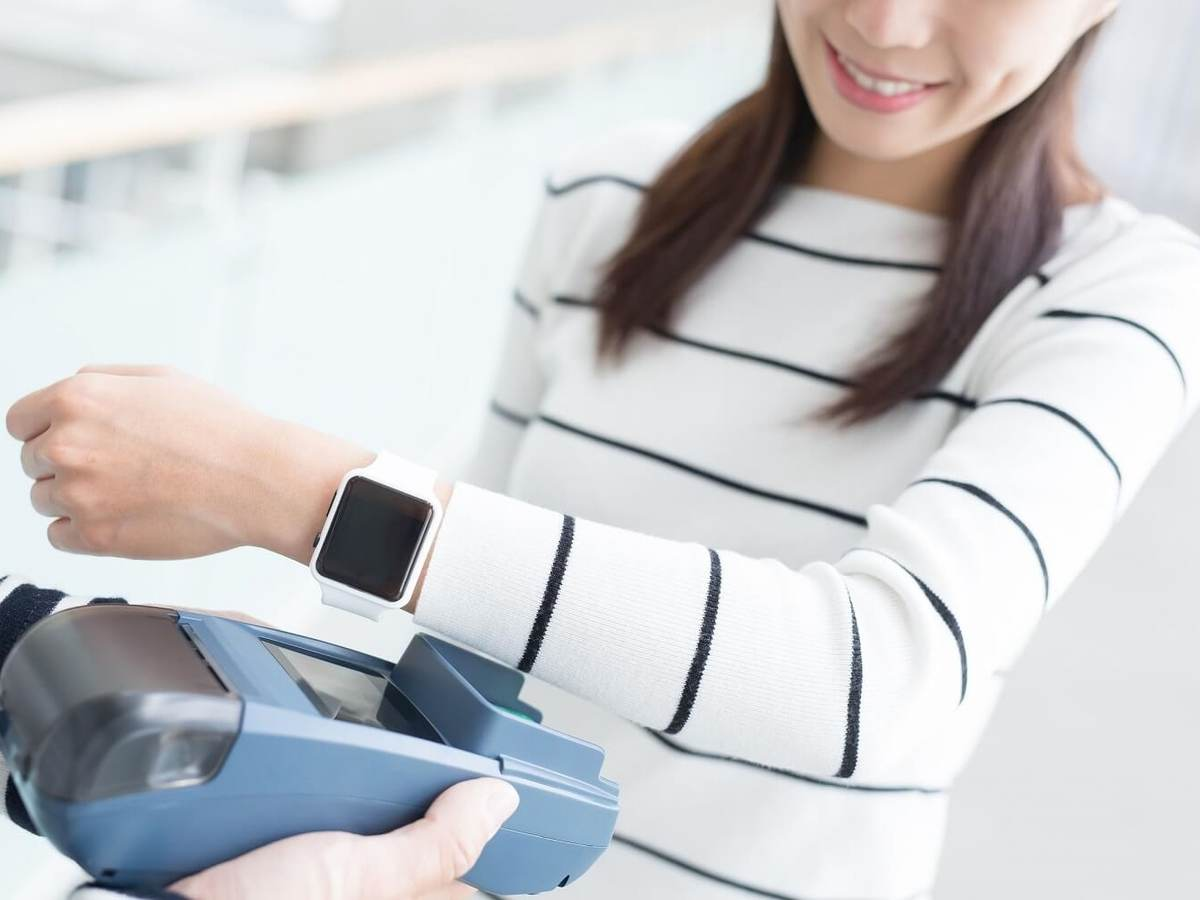 A woman holds her smartwatch up to a grey scanner